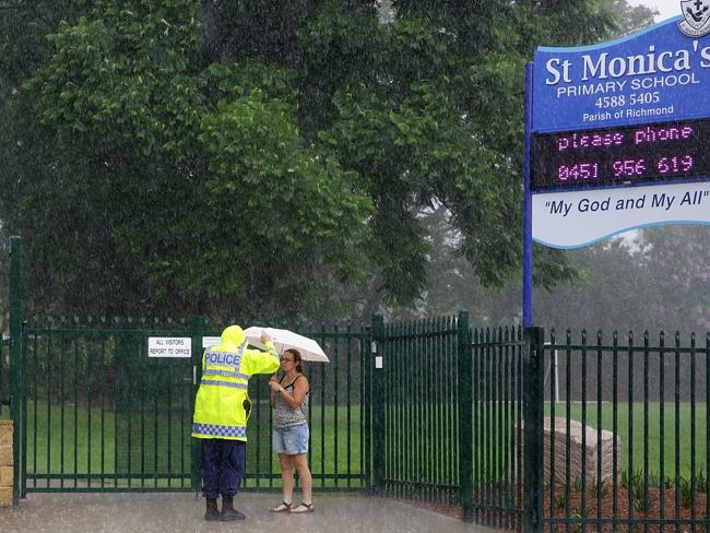 An officer speaks with a concerned parents outside St Monica's Catholic Primary School in