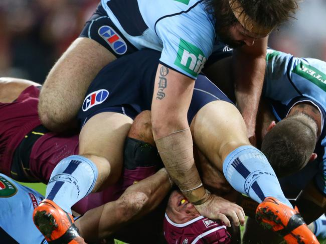 Queensland's Johnathan Thurston is held up over the NSW line. NSW forward Aaron Woods lends a helping hand.