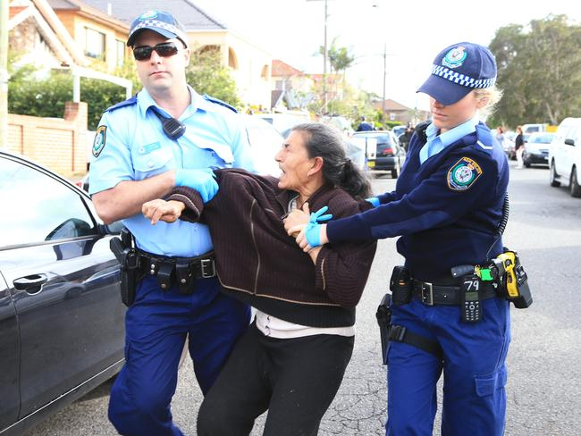Police arrest Mary Bobolas after an alleged assault when the family refused to leave their house after a council-ordered $60,00 clean up. Picture: Adam Taylor