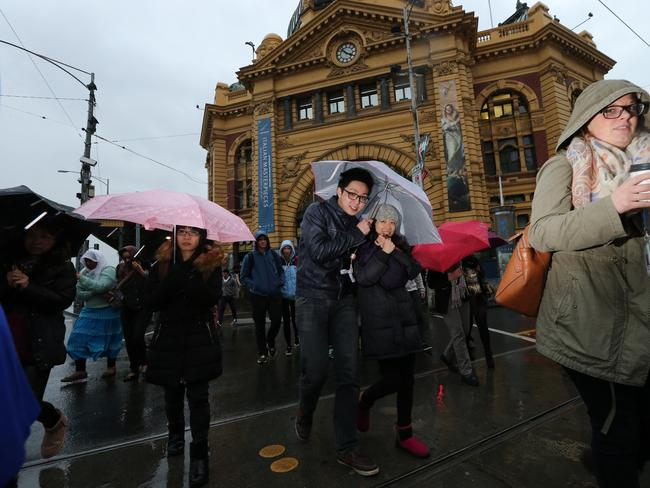 Melburnians seek shelter outside Flinders St Station. Picture: Alex Coppel