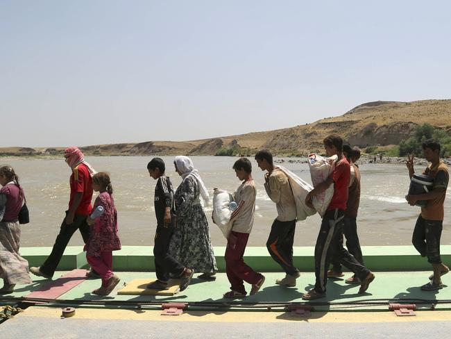 Displaced Iraqis from the Yazidi community cross the Syria-Iraq border at Feeshkhabour bridge over the Tigris River. Pic: AP.