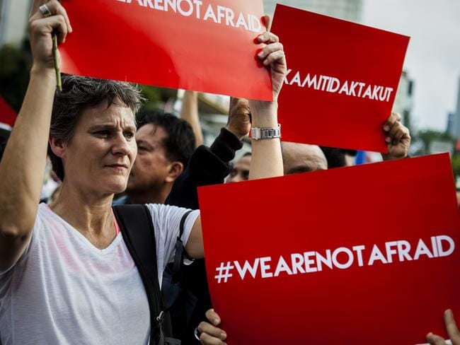 "People hold placards and banners displaying the words ""we are not afraid"" during a rally after the Jakarta terrorist attack in January2016 in Jakarta. Picture: Getty"