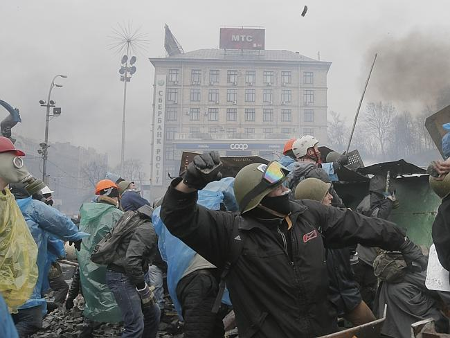 Fighting for freedom ... anti-government protesters throw stones during clashes with riot police in Kiev's Independence Square. Picture: AP