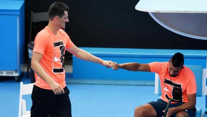 Bernard Tomic of Australia (left) fist pumps Nick Kyrgios of Australia during a practice session at the Australian Open in Melbourne, Saturday, Jan. 14, 2017. (AAP Image/Tracey Nearmy) NO ARCHIVING