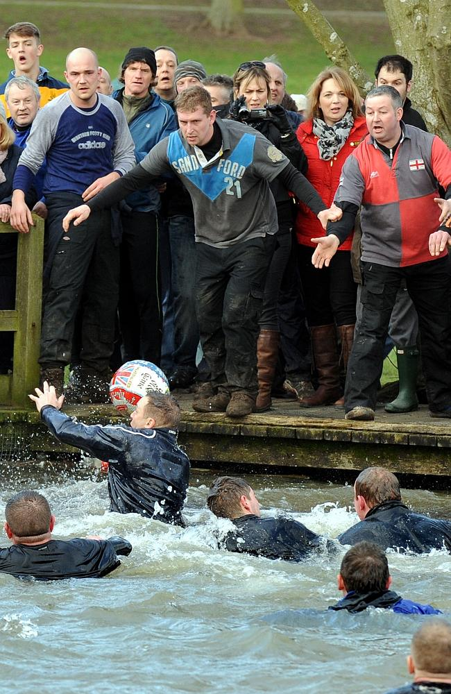 A player throws the ball during the Royal Shrovetide Football match in Ashbourne.