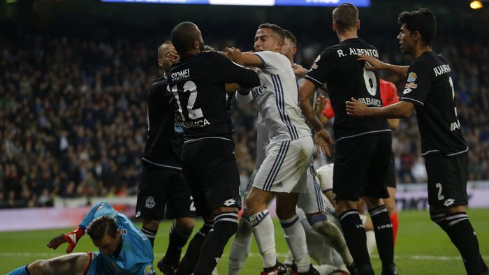 Real Madrid's Lucas Vazquez, centre, scuffles with Deportivo's Sidnei Da Silva, left, during a Spanish La Liga soccer match between Real Madrid and Deportivo Coruna at the Santiago Bernabeu stadium in Madrid, Saturday, Dec. 10, 2016. Real Madrid won 3-2 victory. (AP Photo/Francisco Seco)