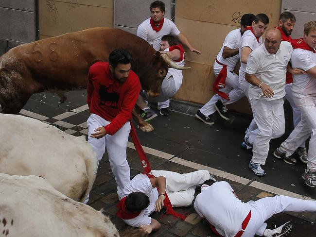 A reveler is tossed by a Miura fighting bull as other fall during the running of the bulls at the San Fermin festival, in Pamplona, Spain, Monday, July 14, 2014. Revelers from around the world arrive to Pamplona every year to take part in some of the eight days of the running of the bulls. (AP Photo/Andres Kudacki)