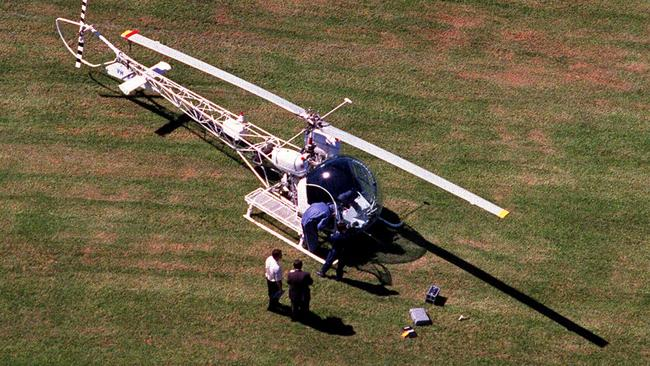 Police inspect the abandoned White Bell 47G helicopter in Ryde's Christie Park which was hijacked by Lucy Dudko. Picture: Troy/Bendeich.
