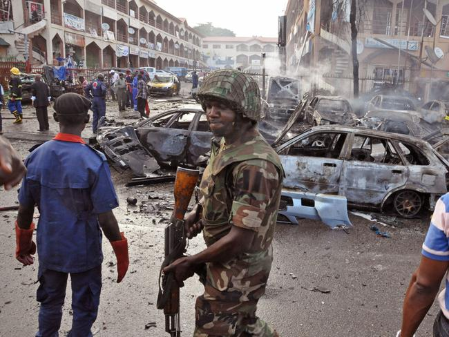 City under siege ... a Nigerian soldier at the scene of a car explosion in Abuja, Nigeria. Picture: Olamikan Gbemiga