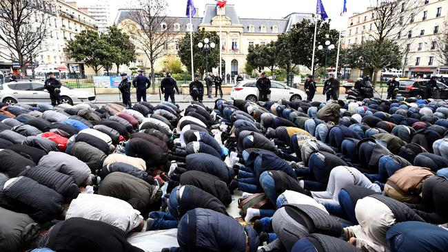 French police watch Muslims praying in the street during a protest in March. Picture: AFP