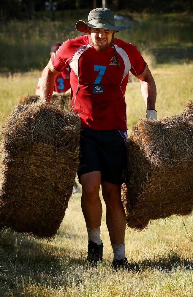 Mitch Garbutt moves hay bales during a Storm training camp.