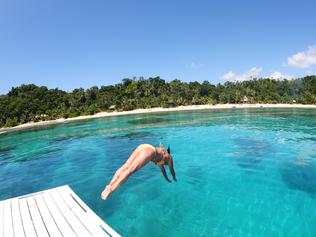 Healthy senior woman dives into tropical water