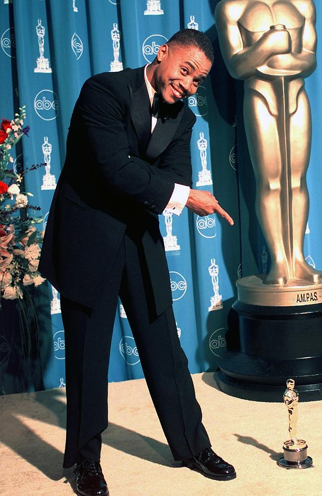 """Cuba Gooding Jr., points to his Oscar for best supporting actor for the film, """"Jerry Maguire,"""" backstage at the 69th annual Academy Awards. (AP Photo/Kevork Djansezian, file)"""