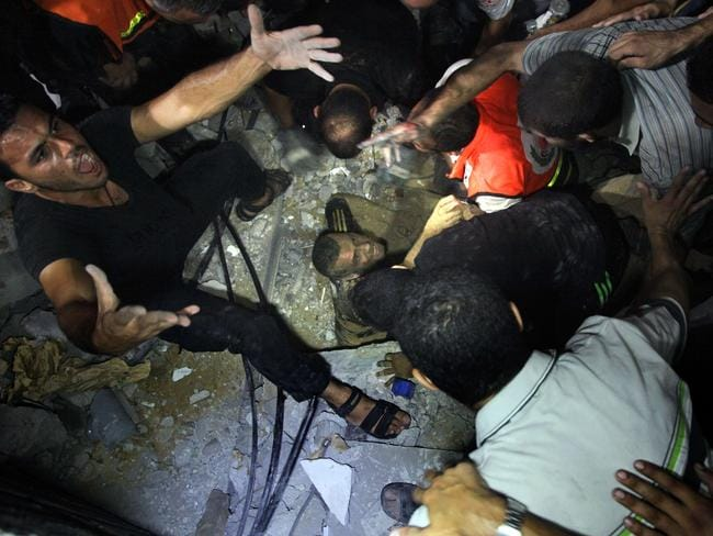 Search ... Palestinian rescues try to dig out an injured man trapped under rubble following an Israeli air strike on a house in Gaza City. Picture: AFP