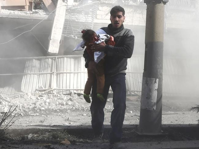 A man carries a girl injured in government bombing in the rebel-held town of Hamouria, in the besieged Eastern Ghouta region. Picture: Abdulmonam Eassa/AFP