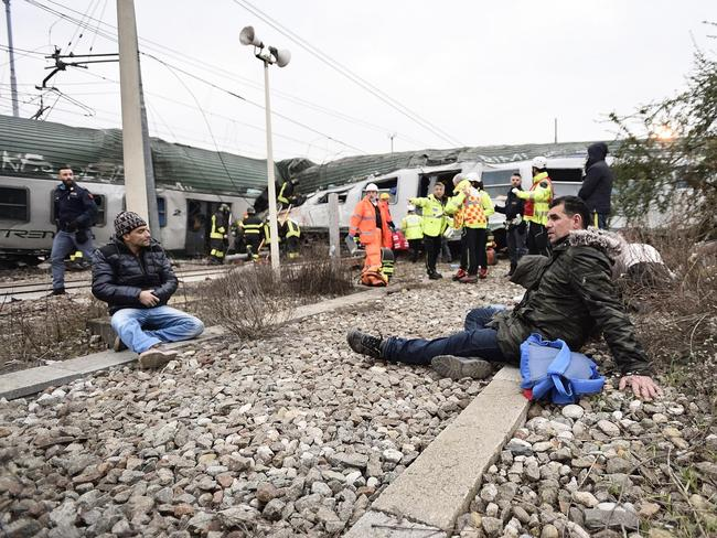 Freed passengers sit on the tracks. Picture: Flavio Lo Scalzo/ANSA via AP