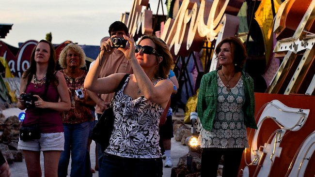 Tourists walk through a display of old hotel and casino signs at sunset at the Neon Museum. Picture: AP
