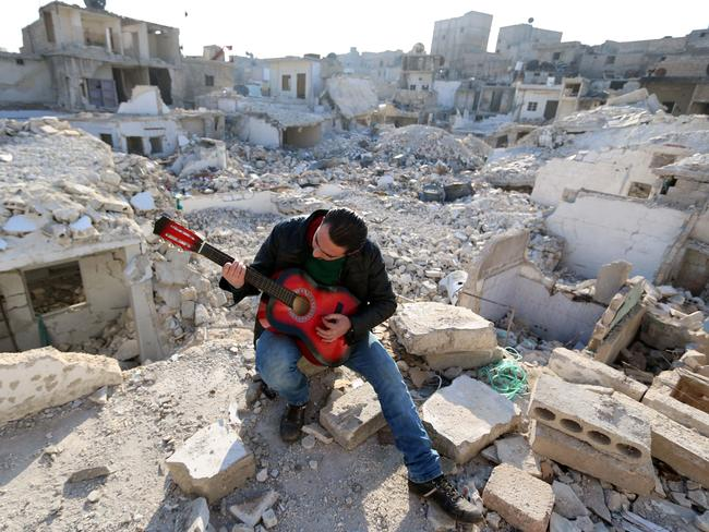 Shehab, a 23-year-old Syrian, practices the guitar amidst the rubble of buildings in the northern Syrian city of Aleppo on December 11, 2015. Photo: AFP PHOTO/Baraa Al-Halabi.