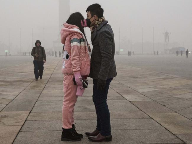 Taking no chances. A couple kisses through face masks in Tiananmen Square last week. Picture: Kevin Frayer/Getty Images
