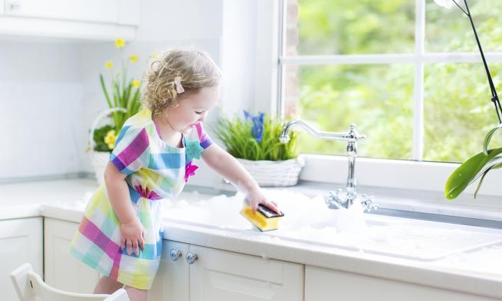 Cute curly toddler girl in a colorful dress washing dishes, clea