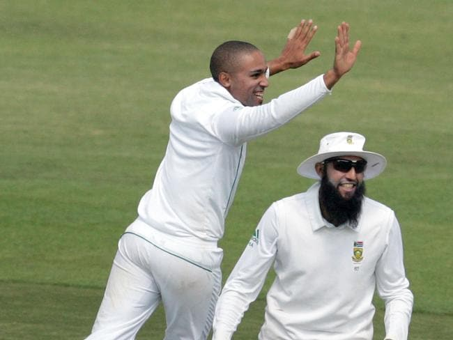 South Africa's bowler Dane Piedt (L) and captain Hashim Amla (R) celebrate a wicket. Picture: AFP