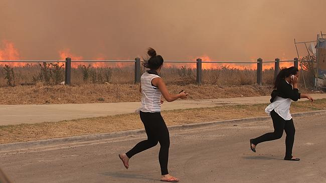 Residents run from a fast moving fire in Craigieburn. Picture: AAP Image/David Crosling