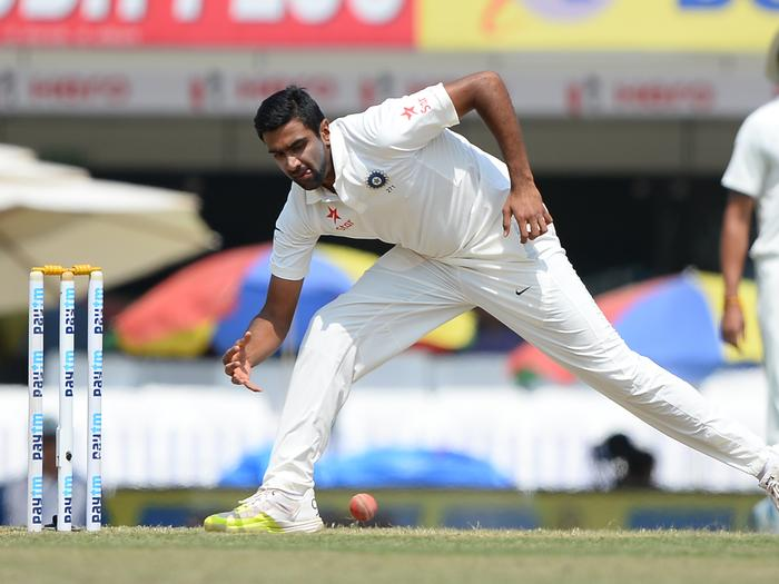 Indian bowler Ravichandran Ashwin stops a ball dur
