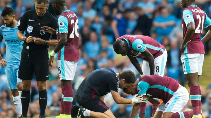 West Ham United's New Zealand defender Winston Reid, (2nd R), is treated after a clash with Manchester City's Argentinian striker Sergio Aguero (L) during the English Premier League football match between Manchester City and West Ham United at the Etihad Stadium in Manchester, north west England, on August 28, 2016. / AFP PHOTO / JON SUPER / RESTRICTED TO EDITORIAL USE. No use with unauthorized audio, video, data, fixture lists, club/league logos or 'live' services. Online in-match use limited to 75 images, no video emulation. No use in betting, games or single club/league/player publications. /