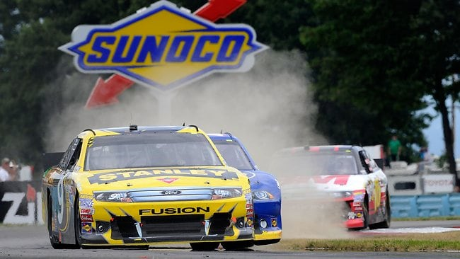 Marcos Ambrose races ahead of Brad Keselowski in the NASCAR Sprint Cup Series Finger Lakes 355 at the Glen at Watkins Glen International.