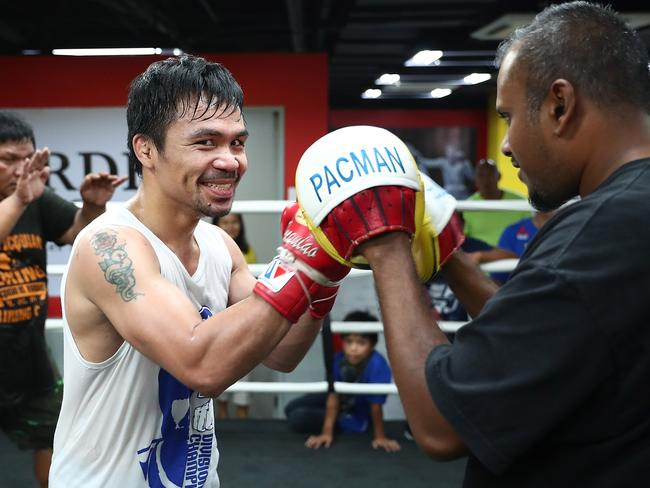 Manny Pacquiao hits the pads with Telegraph journalist Jamie Pandaram. Picture: Getty Images