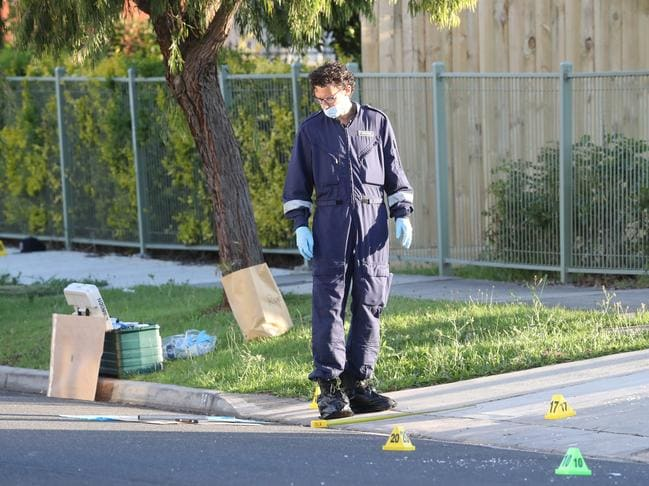 A forensic officer examines a metal pole on the road. Picture: David Crosling