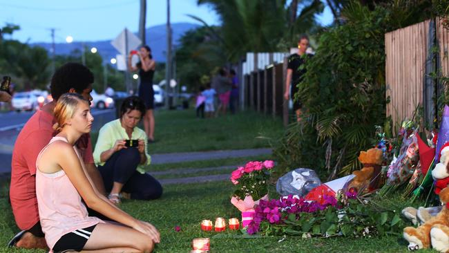 Aaron Oui and Jade Atkinson sit at a vigil of flowers and candles set up opposite the crime scene. Picture: Brendan Radke