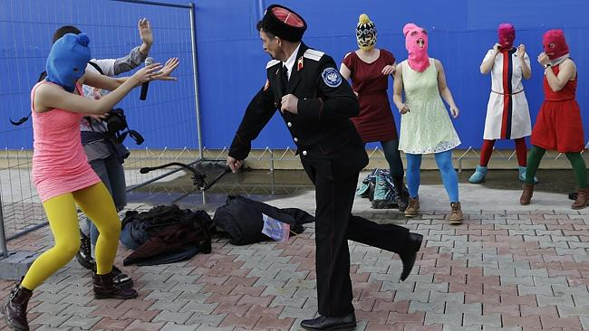 Brutal...A Cossack militiaman attacks Nadezhda Tolokonnikova and a photographer with a whip as she and fellow members of Pussy Riot stage a protest performance in Sochi on Wednesday. Picture: AP