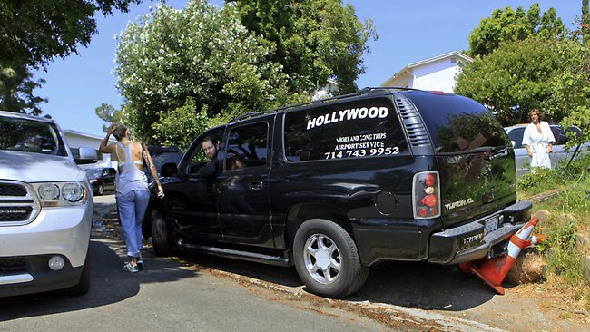 Tempers fray as a tour operator backs over a parking cone in a crowded suburban street below the Hollywood sign. (AP Photo/Damian Dovarganes)