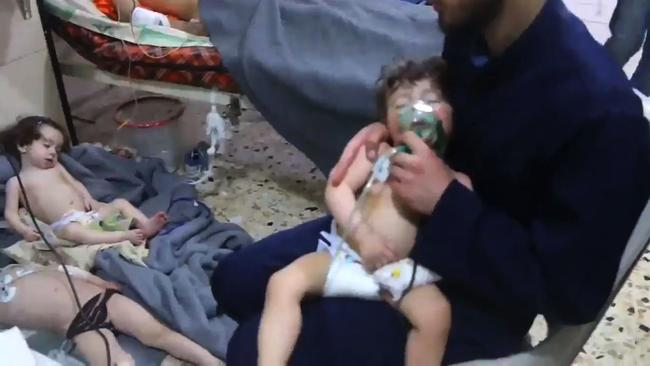 An image grab taken from a video released by the Syrian civil defence in Douma shows an unidentified volunteer holding an oxygen mask over a child's face at a hospital. Picture: AFP