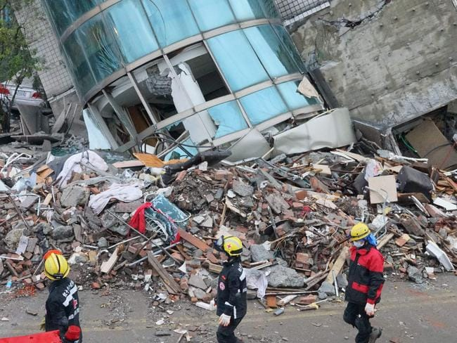 The aftermath : Rescuers walk past a collapsed building in Hualien after the city was hit by a 6.4-magnitude quake. Picture: AFP/Paul Yang