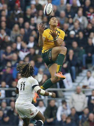 Australia's Israel Folau jumps for the ball as England's Marland Yarde looks on.