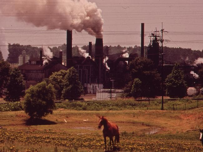 The Atlas Chemical company belches smoke across pasture land in the foreground. The plant was referred to as 'old darky' in the community because black soot from the plant covered everything nearby. One farmer claimed he lost several cows due to soot and chemicals from Atlas. 1972. Picture: Mark St, Gil/Documerica/US National Archives