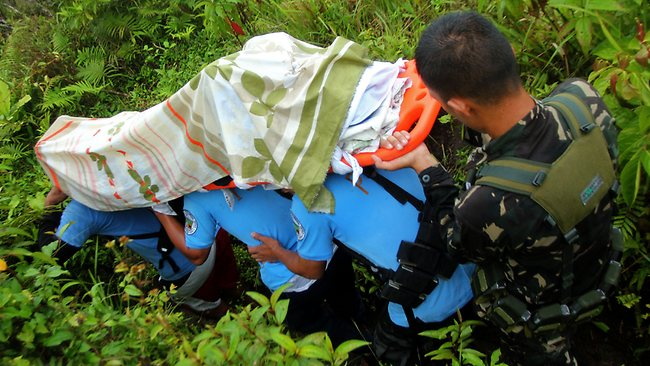 Policemen carry Nicanor Mabao Jr., one of the Filipino tour guides who survived after Mayon Volcano spewed a giant ash cloud, on a stretcher from the slope of Mayon volcano in Legazpi city, Albay province, southeast of Manila on May 7, 2013. Three German tourists and their Filipino tour guide were crushed to death when one of the Philippines' most active volcanoes spewed a giant ash cloud and a hail of rocks on May 7, authorities said. AFP PHOTO/Jay-R Zuniga