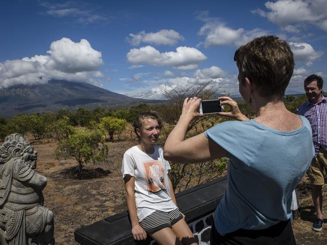 Tourists from Australia take a picture as the background of mount Agung in Bali, Indonesia. Picture: Ulet Ifansasti / Getty