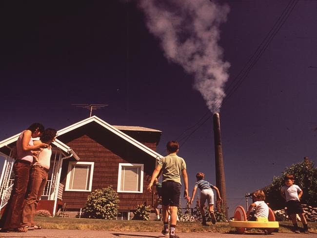 Children play in yard of a Ruston home, while a tacoma smelter stack showers the area with arsenic and lead residue. 1972. Picture: Gene Daniels/Documerica/US National Archives