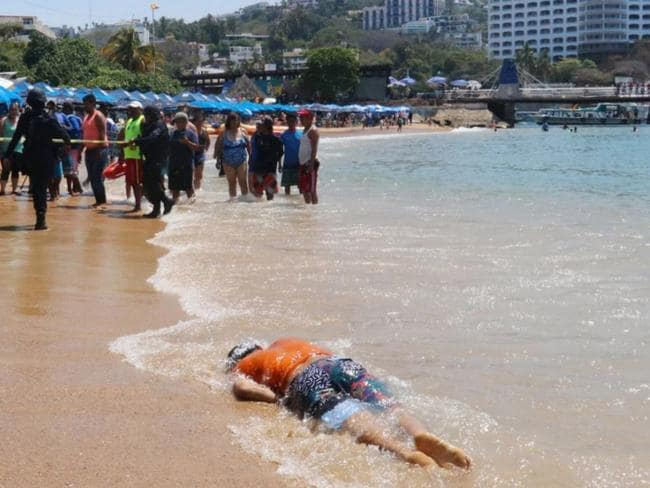 Tourists and residents in Acapulco look on after the body washed up on shore on April 15. Picture: Reuters