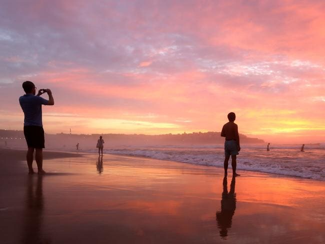 Early morning beachgoers capture the beautiful sunrise at Bondi. Picture: John Grainger