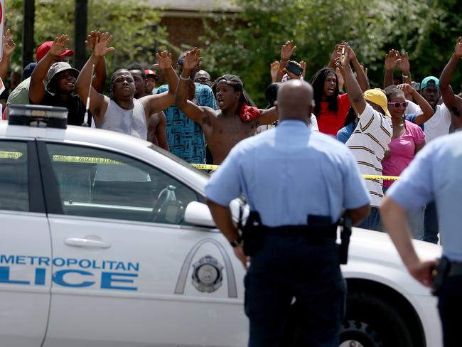 "Crowd gathers ... people raise their arms while chanting, ""Hands up, Don't Shoot"", as they stand nearby to where St Louis police shot and killed a 23-year-old suspect."