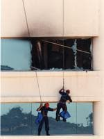 Bomb explosion at the National Crime Authority (NCA) office on the 12th floor of the CPS building in Waymouth Street, Adelaide, 02 Mar 1994. Star Force police officers collecting bomb fragments from a ledge and checking the outside of the building for clues.