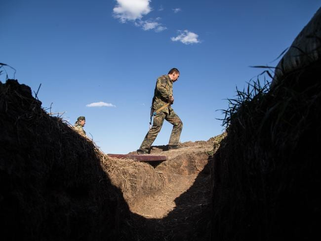 Front line ... A Ukrainian serviceman walks past a trench near Lugansk during shelling. Source: AFP
