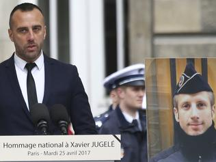 Etienne Cardiles, the partner of slain police officer Xavier Jugele, seen on poster at right, delivers his speech in the courtyard of the Paris Police headquarters, Tuesday, April 25, 2017. France's top officials and presidential candidates are attending a national ceremony to honor the police officer killed by an Islamic extremist on the Champs-Elysees. (AP Photo/Francois Mori)