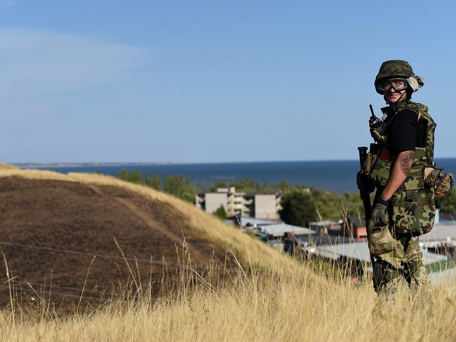 Ukrainian loyalist fighters from the Azov Battalion stand guard on a hill on the outskirts of Mariupol. Picture: Francisco Leong