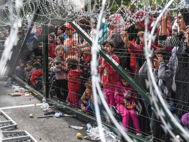Refugees wait at a fence along the Hungarian/Serbian border after it was closed in September 2015. Picture: AFP/Armen Nimani