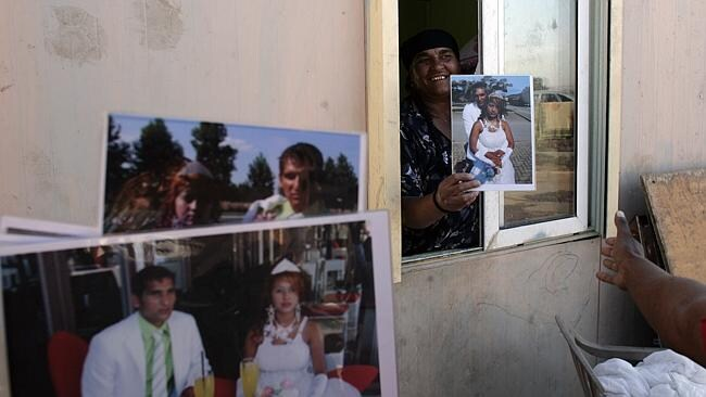 Roma community members display family photos at a Roma settlement north of Athens. Family is central to gypsy culture. Milos Bicanski/Getty Images